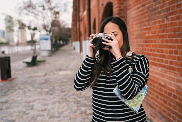 Portret młodej kobiety fotograf na zewnątrz za pomocą profesjonalnego aparatu cyfrowego. koncepcja fotografii