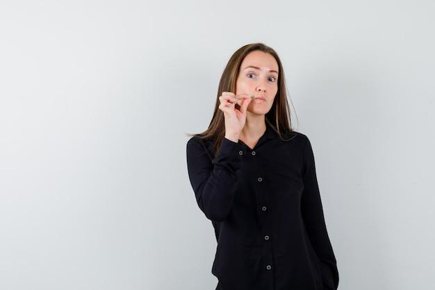 Portret młodej kobiety gest zamka błyskawicznego