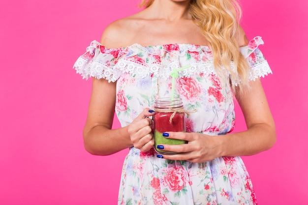 Portret młodej kobiety gospodarstwa i picia smaczny zielony koktajl mleczny na różowym tle.