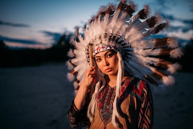 Portret młodej kobiety indian amerykańskich na zachód słońca. cherokee, navajo, kultura zachodnia. nakrycie głowy wykonane z piór dzikiego ptactwa.