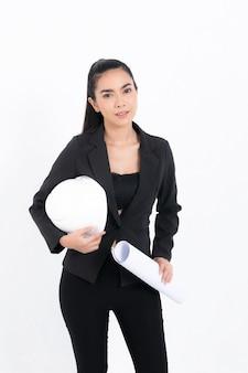 Portret młodej kobiety inżynier ubrana w czarny garnitur, trzymający plan i biały hełm ochronny w studio strzałów na białym tle na białej powierzchni