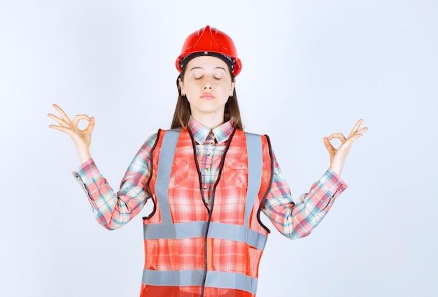 Portret młodej kobiety inżynier w kasku dając aprobaty.