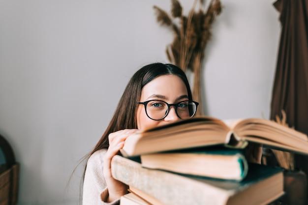Portret młodej kobiety kaukaski studentka w okularach, chowając się za książką