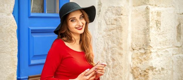 Portret młodej kobiety kaukaski turystycznych w czerwonej długiej sukni i czarnym kapeluszu z walizką, siedząc na schodach na zewnątrz.