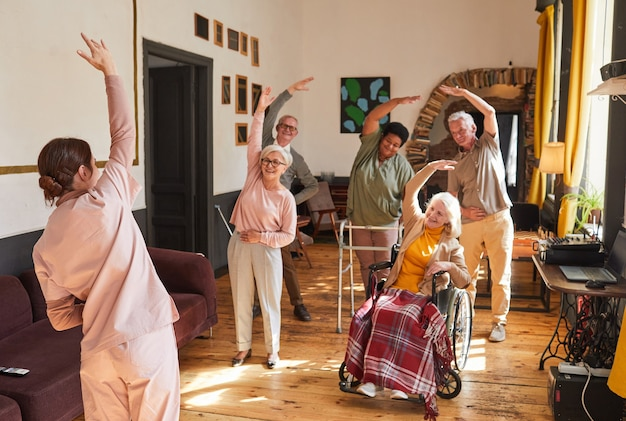 Portret młodej kobiety koordynującej grupę starszych ludzi cieszących się porannymi ćwiczeniami na emeryturze...