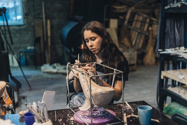 Portret młodej kobiety korzystających z ulubionej pracy w warsztacie. garncarz ostrożnie pracuje nad gliną