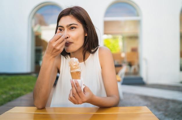 Portret młodej kobiety korzystających ze słonecznej pogody podczas jedzenia lodów na świeżym powietrzu. koncepcja stylu życia.