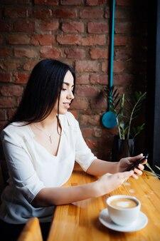 Portret młodej kobiety korzystania z telefonu komórkowego, siedząc w wygodnej kawiarni podczas przerwy w pracy