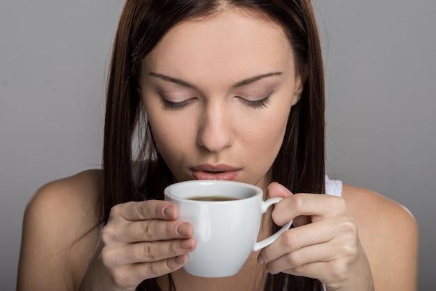 Portret młodej kobiety, która pije kawę.