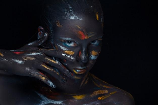 Portret młodej kobiety, która pozuje pokryta czarną farbą