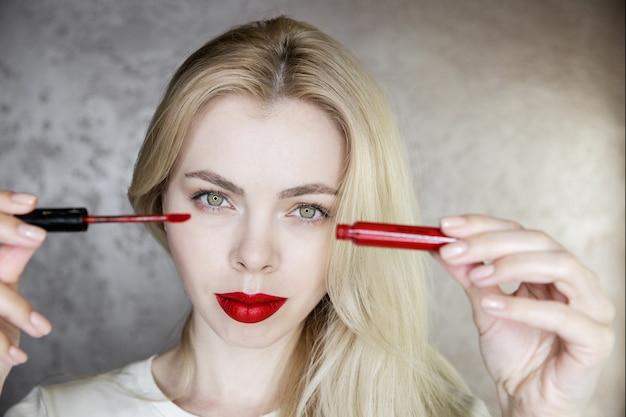 Portret młodej kobiety, która robi makijaż z jaskrawoczerwonymi ustami