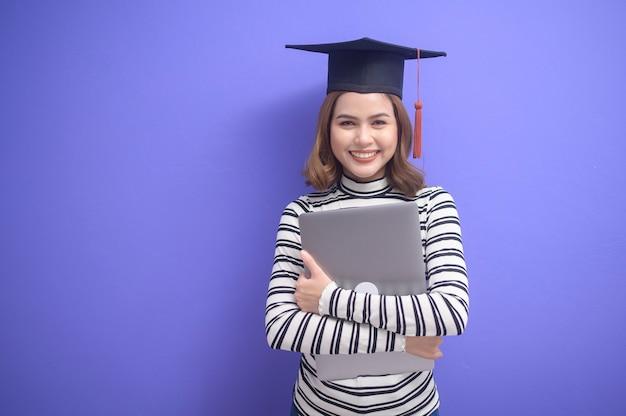 Portret młodej kobiety, która ukończyła studia na niebieskim tle