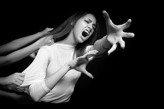 Portret młodej kobiety, która z przerażeniem i strachem próbuje uciec z wielu rąk, ciągnąc ją do tyłu i rozrywając. pojęcie samotności, straty, strachu. straszny i okropny portret