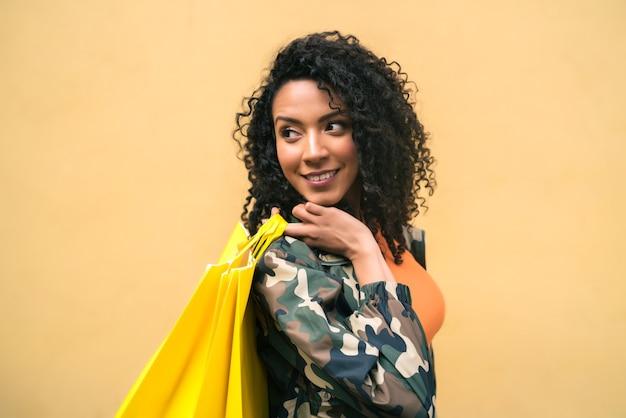 Portret młodej kobiety łacińskiej afro american gospodarstwa torby na zakupy na żółtym tle. koncepcja sklepu i stylu życia.