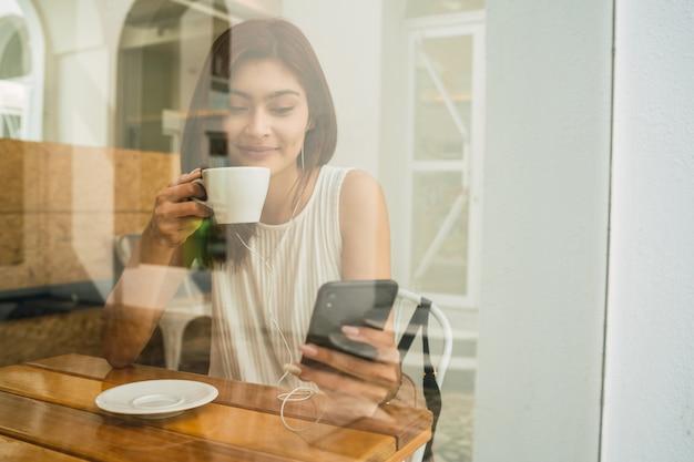 Portret młodej kobiety łacińskiej przy użyciu swojego telefonu komórkowego, siedząc w kawiarni. koncepcja komunikacji.