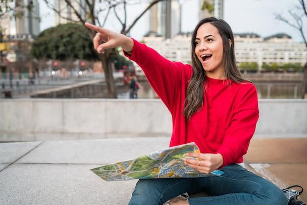 Portret młodej kobiety łacińskiej z mapą i wskazując gdzieś, szukając wskazówek, na zewnątrz na ulicy. koncepcja podróży.