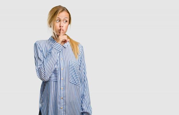 Portret młodej kobiety ładna blondynka, utrzymując sekret lub prosząc o ciszę, poważną twarz, pojęcie posłuszeństwa