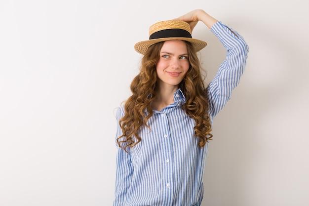 Portret młodej kobiety ładny kapelusz słomkowy dżinsy niebieska bawełniana koszula pozowanie na białej ścianie