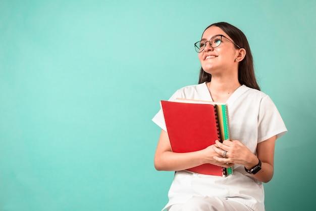Portret młodej kobiety latinx w mundurze zdrowotnym trzymającym książki
