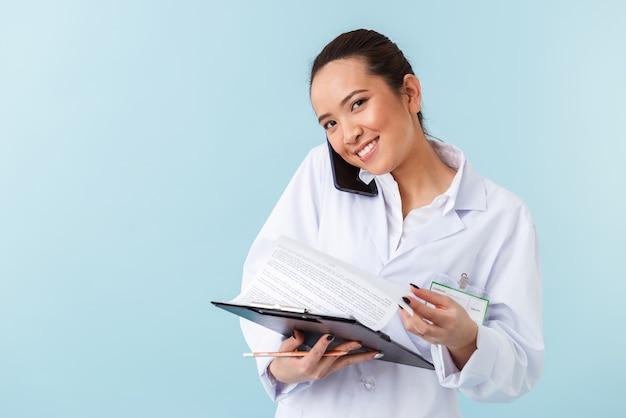 Portret młodej kobiety lekarz pozowanie na białym tle nad niebieską ścianą trzymając schowek rozmawia przez telefon komórkowy.