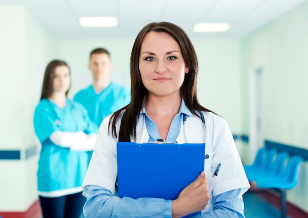 Portret młodej kobiety lekarz ze stażystami