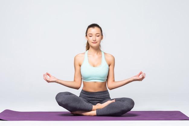 Portret młodej kobiety medytacji w pozie lotosu na białym tle