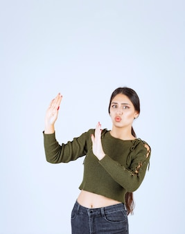 Portret młodej kobiety modelu wpychając coś w bok nad białą ścianą.