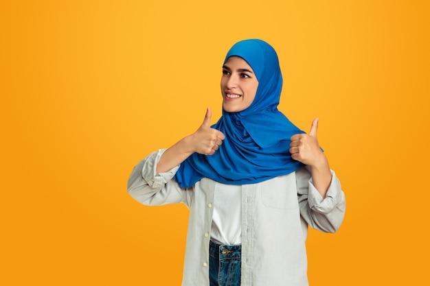 Portret młodej kobiety muzułmańskiej na białym tle na żółtym tle studio