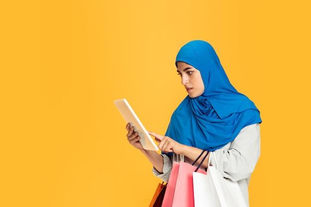 Portret młodej kobiety muzułmańskiej odizolowanej na żółtym tle studia