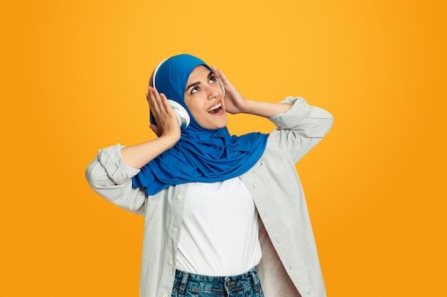 Portret młodej kobiety muzułmańskiej odizolowanej na żółtym tle studyjnym