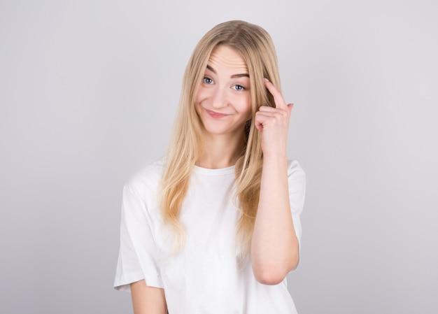Portret młodej kobiety myśli z palcem na głowie na białym tle na szarej ścianie