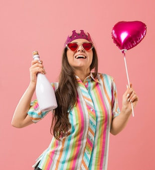 Portret młodej kobiety na imprezie z balonem i butelką szampana