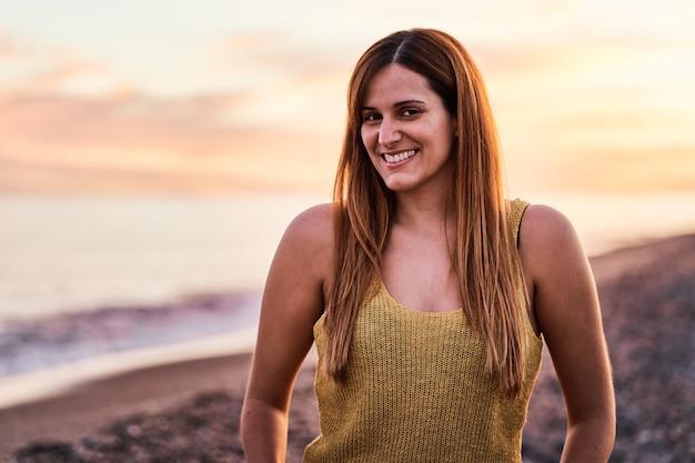 Portret młodej kobiety na plaży o zachodzie słońca