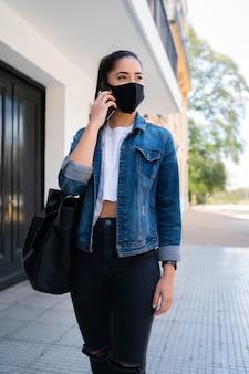 Portret młodej kobiety na sobie maskę i rozmawia przez telefon, stojąc na zewnątrz na ulicy. koncepcja miejska. nowa koncepcja normalnego stylu życia.