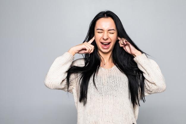 Portret młodej kobiety nakrycie rękami wręcza jej ucho, odizolowywający nad biel ścianą