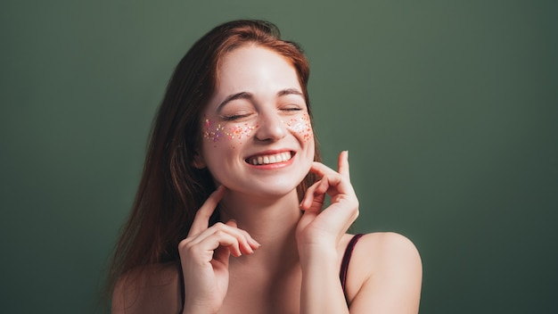 Portret młodej kobiety. niezręczny uśmiech zębów. ruda suczka z zamkniętymi oczami