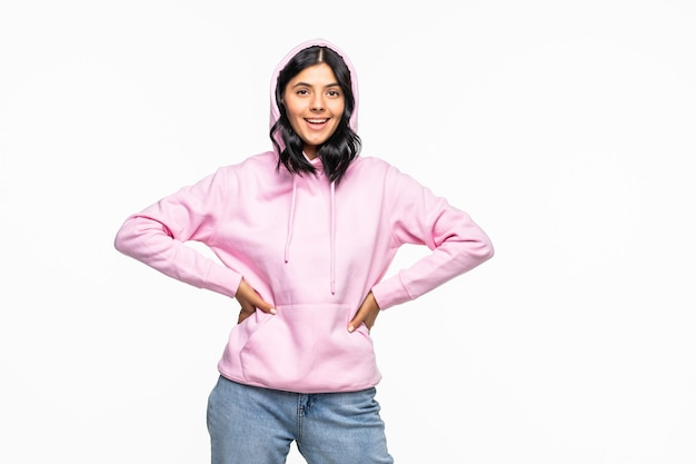 Portret młodej kobiety nosi bluzę z kapturem, pozującą na białej ścianie