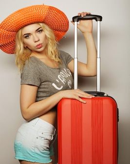 Portret młodej kobiety noszącej duży słomkowy pomarańczowy kapelusz stojący z pomarańczową torbą podróżną