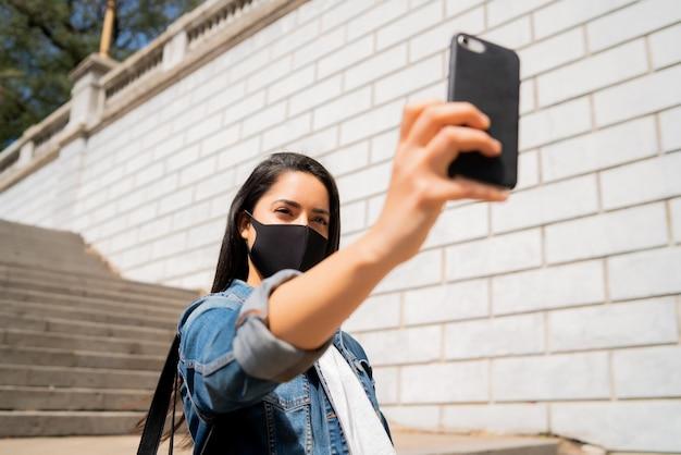 Portret młodej kobiety noszącej maskę i robienia selfie ze swoim telefonem mophile stojąc na zewnątrz. koncepcja miejska. nowa koncepcja normalnego stylu życia.