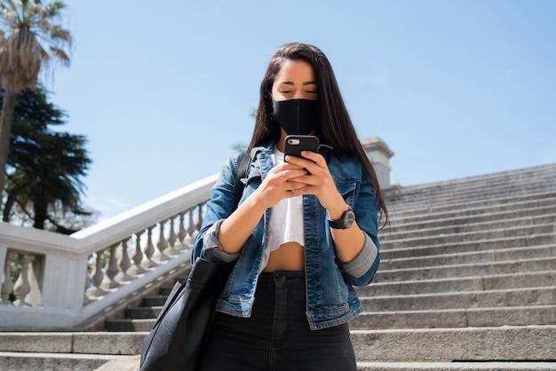 Portret młodej kobiety noszącej maskę ochronną i korzystającej z telefonu komórkowego, stojąc na zewnątrz na ulicy. nowa koncepcja normalnego stylu życia. koncepcja urbanistyczna.