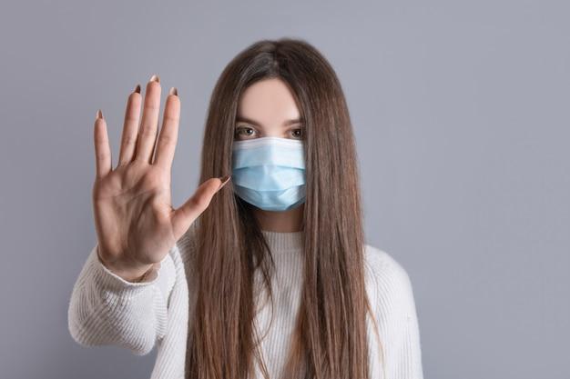 Portret młodej kobiety noszącej medyczną maskę ochronną pokazuje gest ręki, aby zatrzymać pandemię koronawirusa, kobieta w osłonie twarzy stoi przed epidemią wirusa covid-19, opieka zdrowotna, koncepcja epidemii.