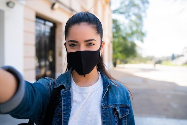 Portret młodej kobiety noszenia maski i robienia selfie na zewnątrz