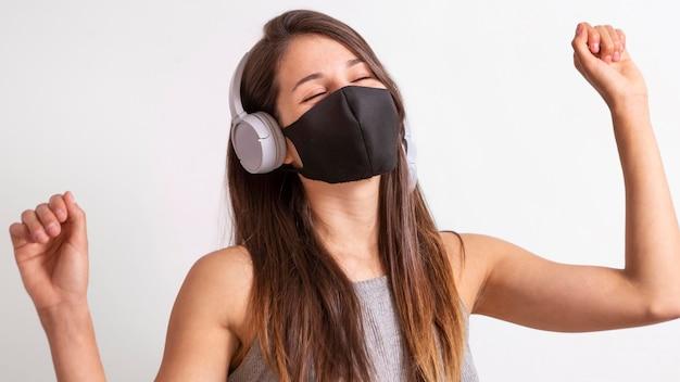 Portret młodej kobiety noszenia maski i słuchania muzyki