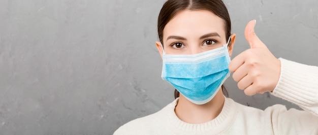 Portret młodej kobiety noszenia maski medyczne. osoba jest szczęśliwa, ponieważ w końcu jest zdrowa. chroń swoje zdrowie. koncepcja koronawirusa