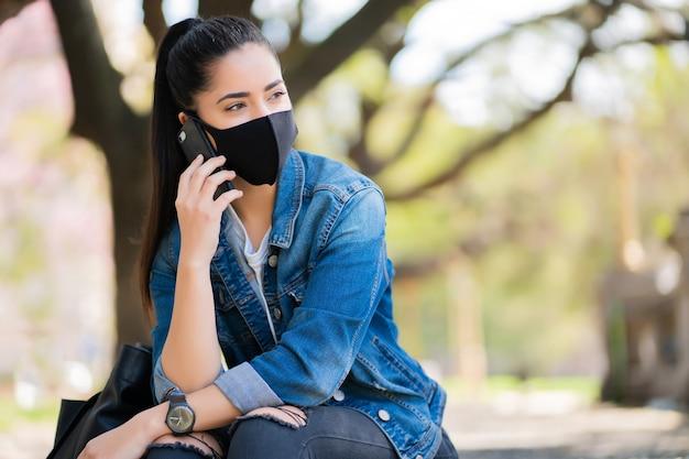 Portret młodej kobiety noszenie maski i rozmawia przez telefon, siedząc na schodach na zewnątrz. koncepcja miejska