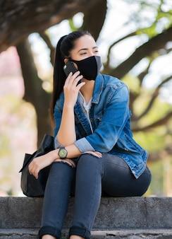 Portret młodej kobiety noszenie maski i rozmawia przez telefon, siedząc na schodach na zewnątrz
