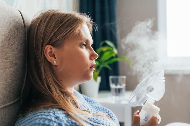Portret młodej kobiety o blond włosach robi inhalację z nebulizatorem parowym w domu