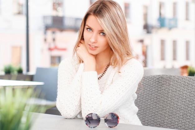 Portret młodej kobiety o pięknych niebieskich oczach z uśmiechem o blond włosach z naturalnym makijażem w sweter vintage w letniej kawiarni na budynkach. atrakcyjna dziewczyna.