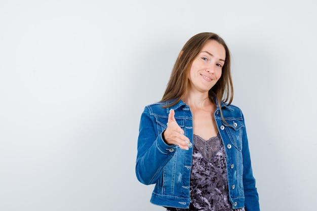 Portret młodej kobiety oferującej uścisk dłoni na powitanie w dżinsowej kurtce, sukience i delikatnym widoku z przodu