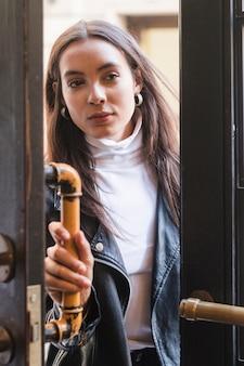 Portret młodej kobiety, otwierając klamkę